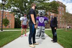 President Julie Sullivan and Tommie talk with a student during Labor Day weekend.