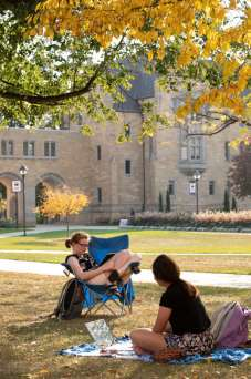 Keeli Gustafson, left, and a friend study below a tree on the lower quad on a beautiful fall afternoon during Homecoming week. Mark Brown/University of St. Thomas