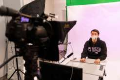 Student Joey Swanson reads from a telepromter in the TommieMedia studio in O'Shaughnessy Education Center. Mark Brown/University of St. Thomas