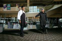 Dining services staffers Carl Littlejohn, left, and brother Anthony Littlejohn, right, pose for a photo in the Anderson Student Center. They were part of a team of critical employees ensuring that students and staff remaining on campus were looked after during the start of the pandemic.