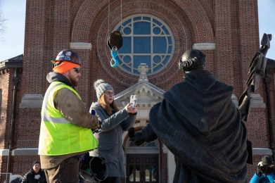 Art History Professor Victoria Young takes photos as a construction crew installs the new sculpture of St. Thomas Aquinas by Canadian artist Timothy P. Schmalz. Mark Brown/University of St. Thomas