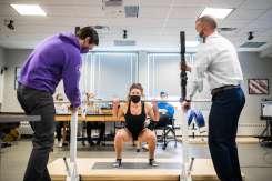 Professor Adam Korak, right, and Ben Nichols, left, help adjust the barbell rack as student Estee Frantz demonstrates the use of motion capture technology. Liam James Doyle/University of St. Thomas