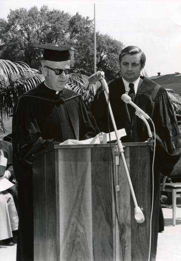 Monsignor Terrence Murphy presents Senator Walter Mondale with an honorary degree at the College of St. Thomas spring 1973 commencement ceremony.