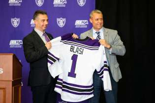 Rico Blasi is given his own University of St. Thomas hockey jersey by director of athletics Phil Esten during a press conference in the James B. Woulfe Alumni Hall on April 6, 2021 in St. Paul. Blasi will become the University's first Division-I hockey coach. Liam James Doyle/University of St. Thomas