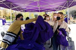 Peggy Jerabek, left, with Student Diversity and Inclusion Services, hands out hoodies to seniors during Grad Fest. Mark Brown/University of St. Thomas