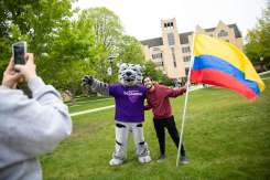 An international Freshman student takes a photo with Tommie.