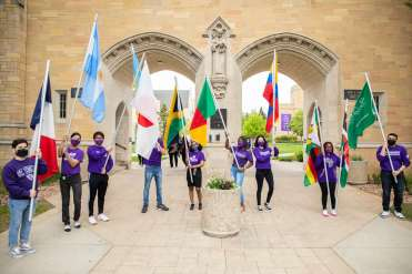 International Freshman students pose with their respective country's flags.