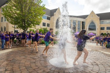 Students celebrate by running through the water fountain on Monahan Plaza after the annual March Out of the Arches event. Mark Brown/University of St. Thomas