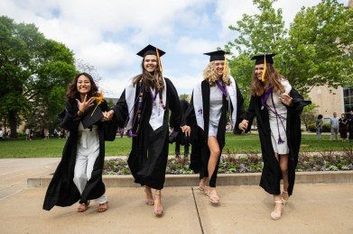 Students jump for family photos after the College of Arts and Sciences commencement ceremony. Mark Brown/University of St. Thomas