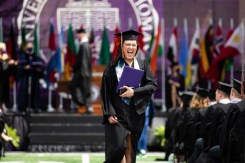 A student celebrates after getting a diploma during the Opus College of Business undergraduate commencement ceremony. Mark Brown/University of St. Thomas