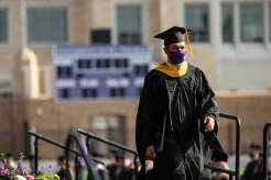 A student walks across the stage during the commencement ceremony for graduate programs in the Opus College of Business and School of Engineering. Mark Brown/University of St. Thomas