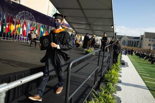 A student walks across stage during the commencement ceremony for graduate programs in the Opus College of Business and School of Engineering. Mark Brown/University of St. Thomas