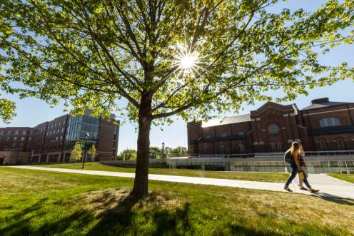 The sun shines through a tree over Aquinas Chapel, the Iversen Center for Faith and Tommie North Residence Hall on a beautiful sunny spring morning. Mark Brown/University of St. Thomas