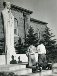 Two students praying at the Our Lady Queen of Peace Shrine, circa 1950.