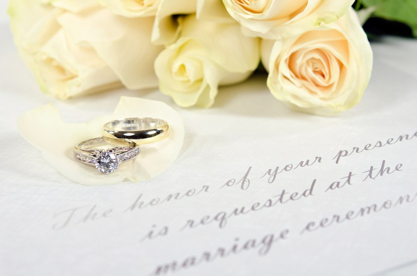 Wedding ring and engagement rings and yellow roses