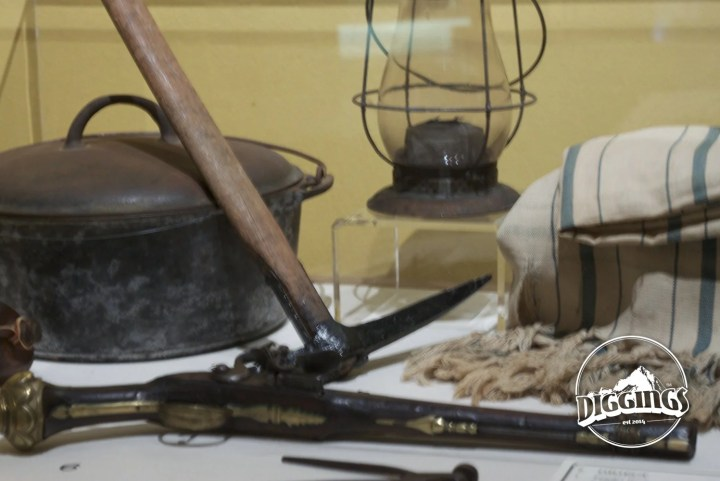 Display of common tools that gold miners would have had during the California Gold Rush, including: pick, dutch oven, lamp, blanket, and pistol.