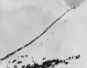 Miners climb, in single file, up the forbidding 45° trail of Chilkoot Pass.