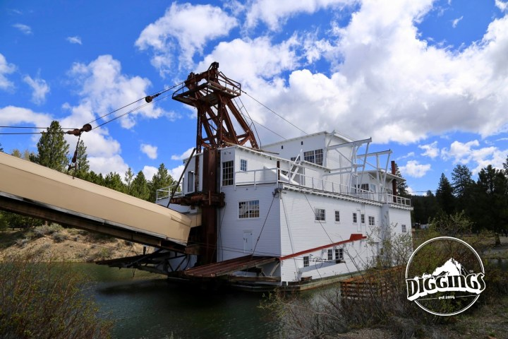 "A rear view of the dredge with the covered ""stacker"" hovering over the dredges last tailings at the Sumpter Valley Dredge State Heritage Area"