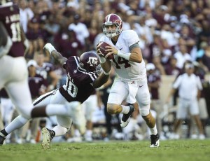 Oct 17, 2015; College Station, TX, USA; Alabama Crimson Tide quarterback Jake Coker (14) runs with the ball during the fourth quarter as Texas A&M Aggies defensive lineman Daeshon Hall (10) attempts to make a tackle at Kyle Field. The Crimson Tide defeated the Aggies 41-23. Mandatory Credit: Troy Taormina-USA TODAY Sports