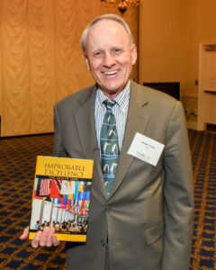 George La Noue holds his book Improbable Excellence at a reception for UMBC alumni in Annapolis.