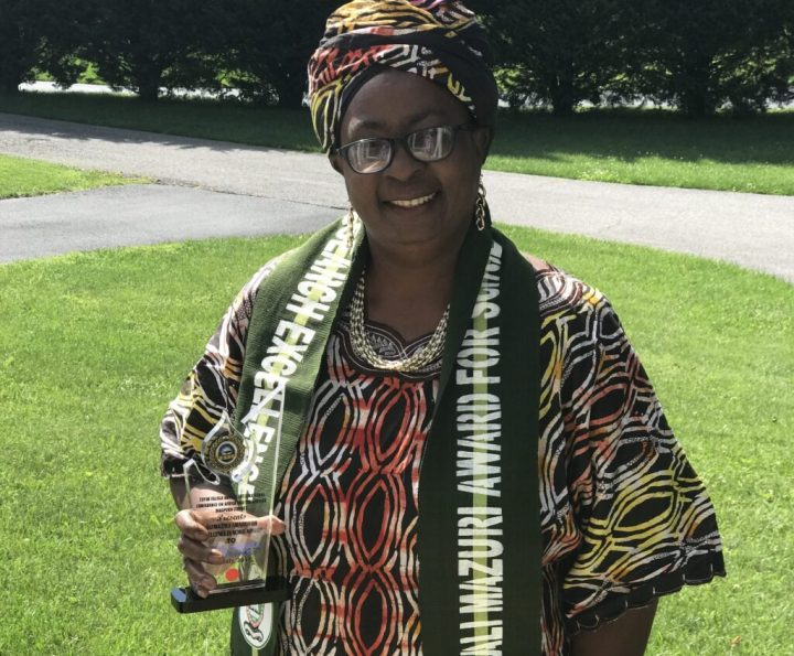 Adult woman wearing Nigerian clothing and head piece holds a glass award in her right hand as she smiles at camera, green fields and trees are behind her