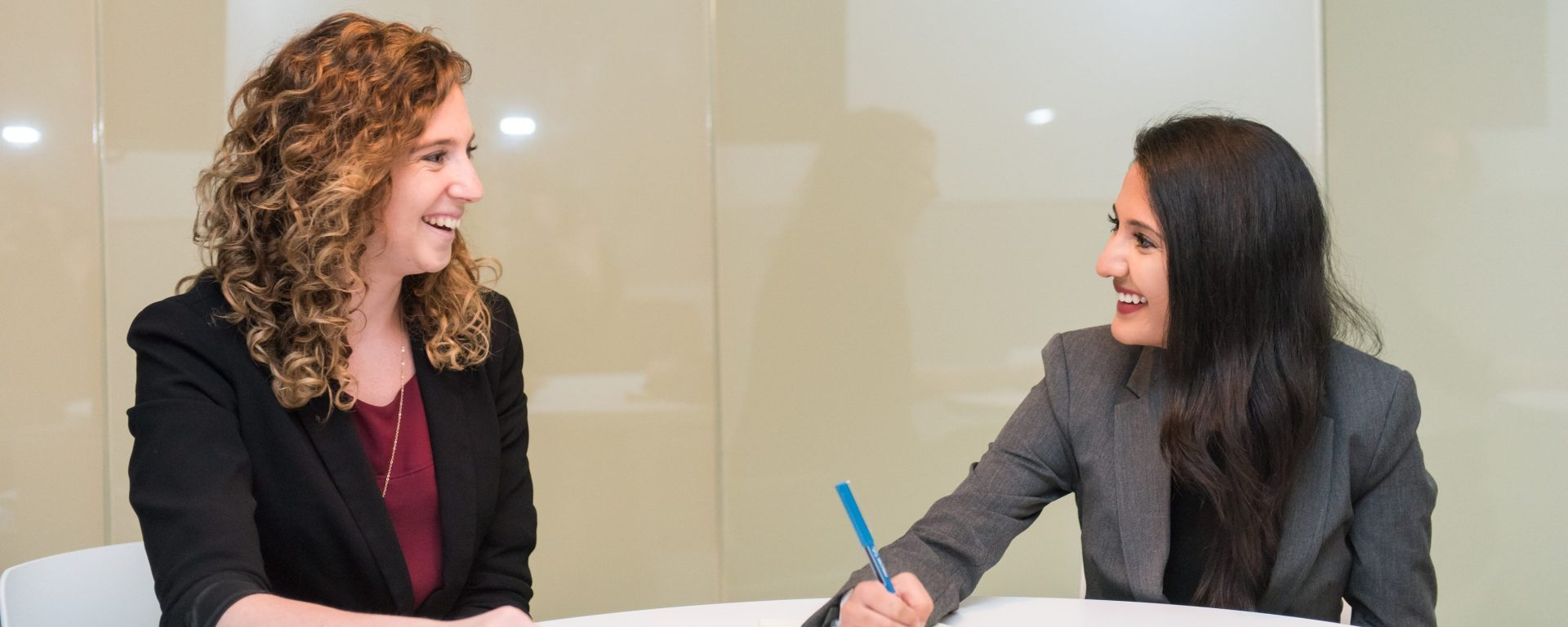Two women in blazers sit at a small conference table, facing each other and smiling. One is writing on a pad of paper.