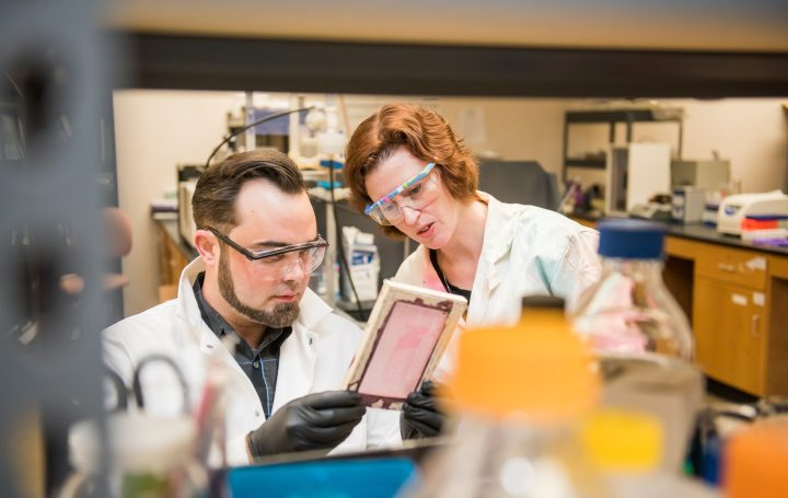 White man with dark beard and white woman with red hair look at a sample in a lab. Both wear lab coats and goggles.