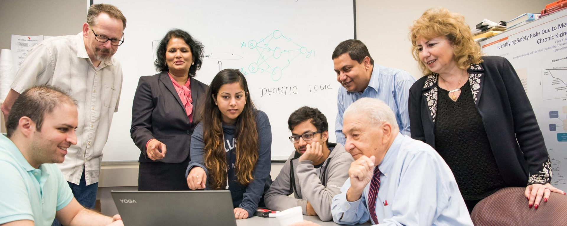 A diverse group of students and professors clusters around a laptop screen in a conference room.