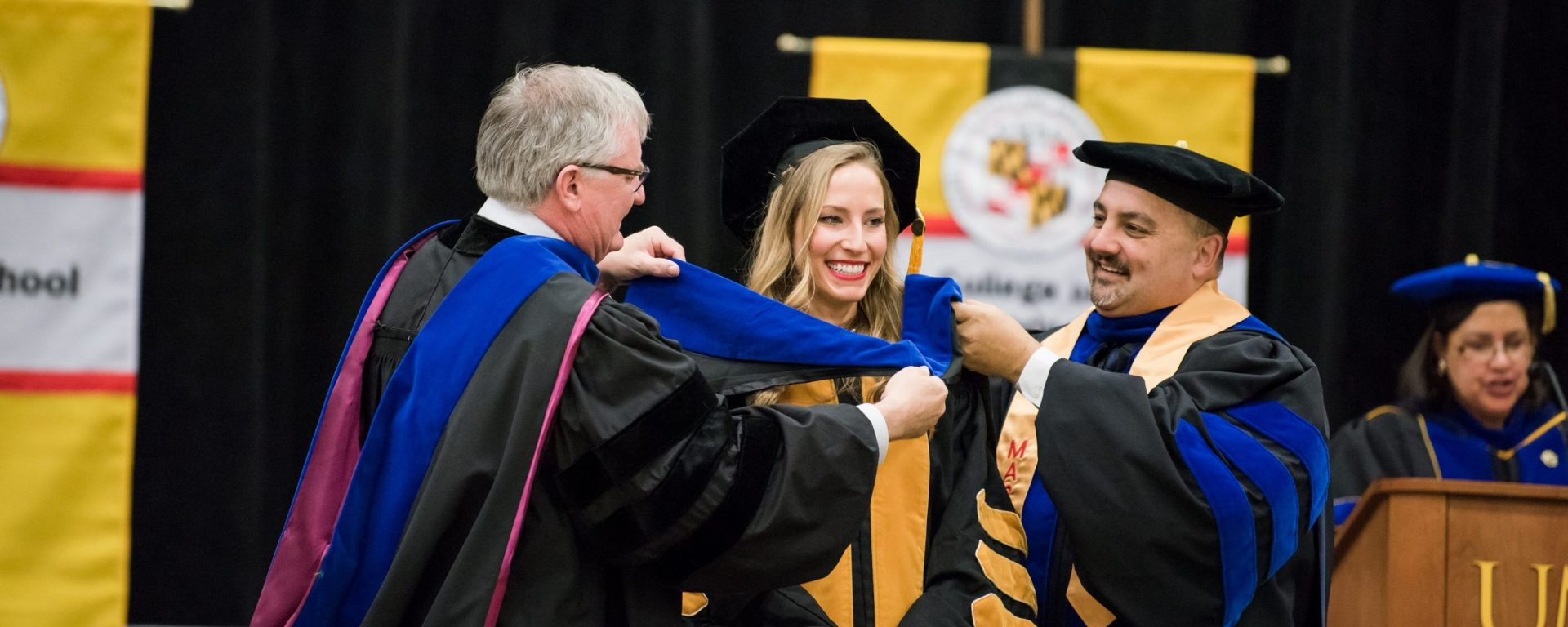 Student receives her PhD in hooding ceremony with faculty member and provost