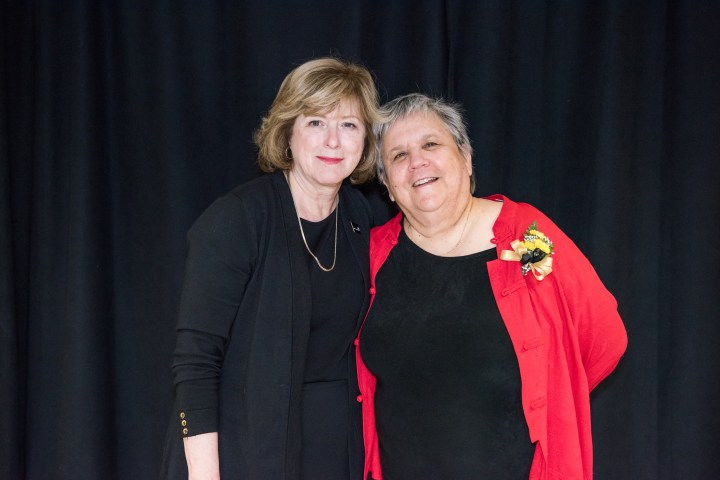 Two women pose together, smiling, in front of black backdrop