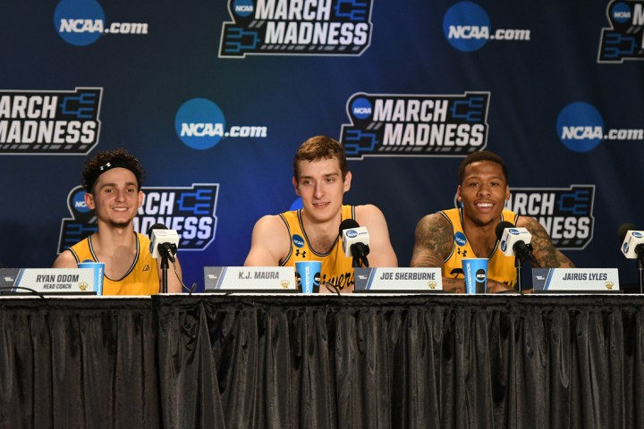 Three basketball players speak into microphones in front of March Madness backdrop.