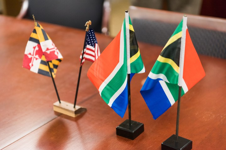 Maryland, U.S., and South African flags adorn the conference table at the partnership event.