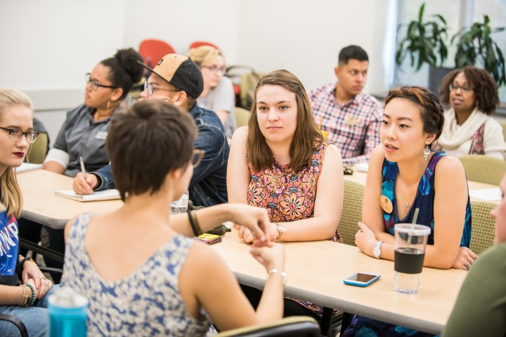 Several college students gather around a table, in conversation