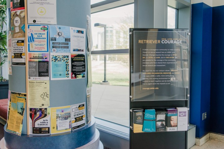 A station provided support resources for survivors of sexual violence and related educational materials. Station is black with white and gold type, featuring trifold flyers in a container.