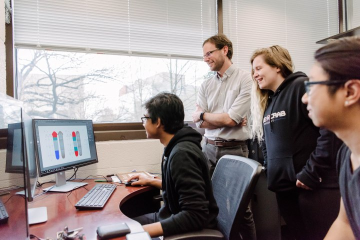 Faculty member and three students gathered around a computer showing figures of planaria worms.