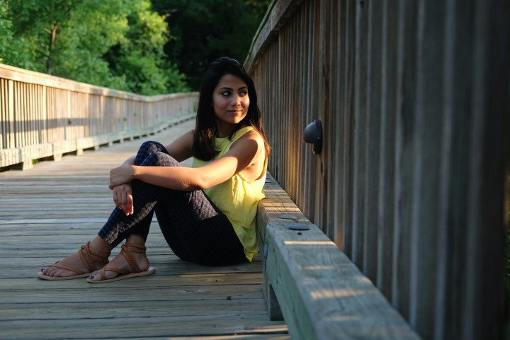 A woman in a yellow shirt, jeans, and sandals sits on a wooden bridge, with trees in the background.
