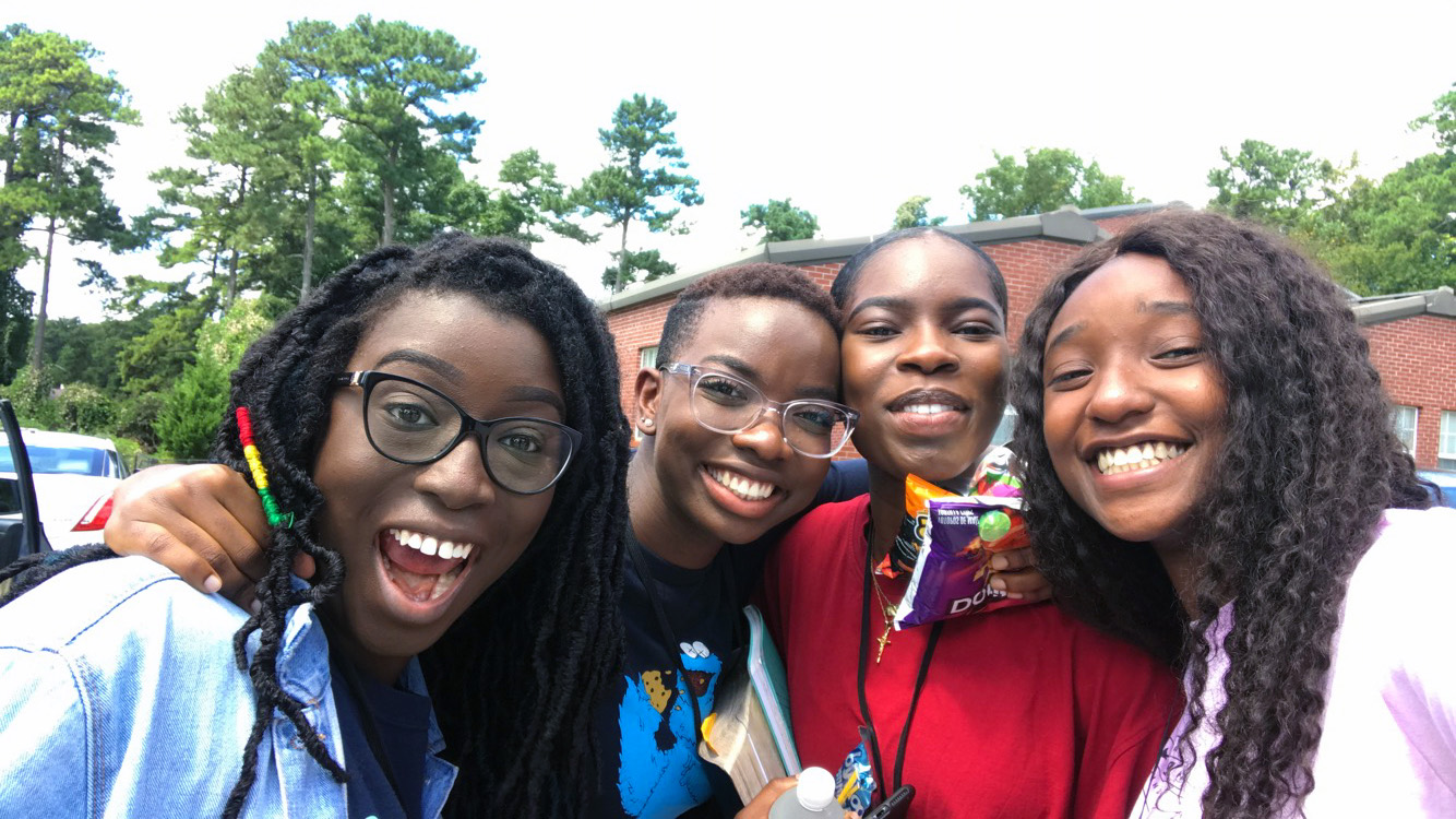 Four women take a selfie outside, in front of a brick building and trees, smiling.