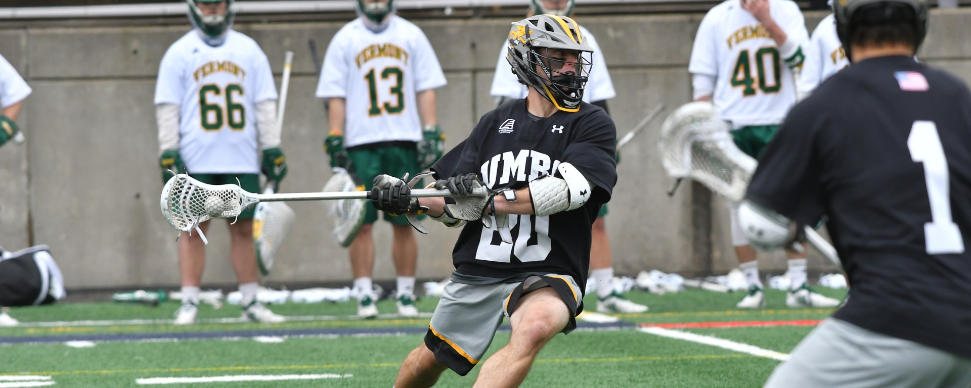 Men's lacrosse player in action on the field, as players from the opposing team stand in the background.