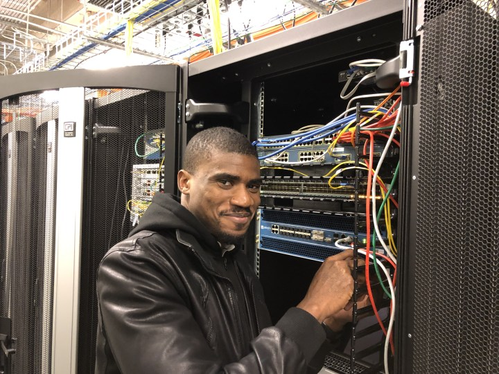 Man stands in front of powerful computing equipment, moving cables.