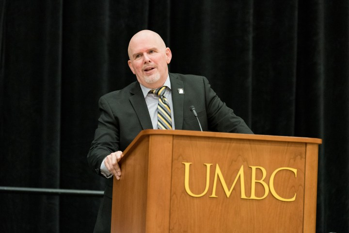 "Middle-aged white man with white beard and mustache speaks at podium. Podium reads ""UMBC."" Man wears a dark suit and striped tie."