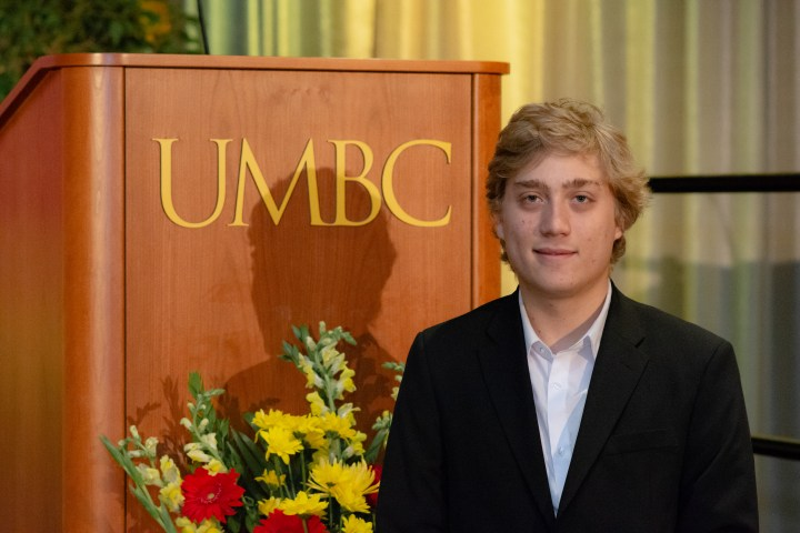 """Young man with blonde hair stands in front of podium reading """"UMBC."""" He wears a suit jacket."""