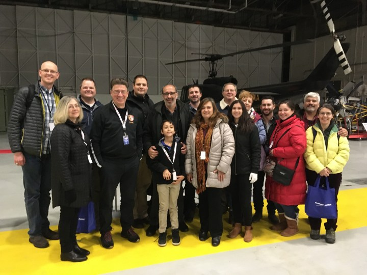 Group of 16 people of all ages stand, smiling, inside a hangar, with a helicopter in the background.