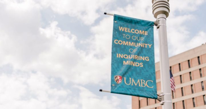 "Sign on a pole reads ""Welcome to our community of inquiring minds"" with UMBC logo."