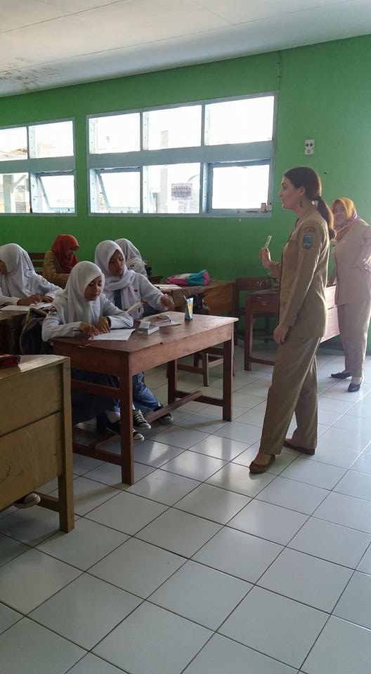 A young woman from the U.S. wearing a khaki uniform stands in front of a class of young teenage girls wearing white hijabs and sitting behind wooden desks in a bright green classroom with many windows along the side wall.