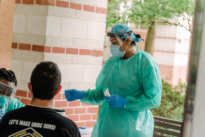 Young person sits near medical professional in protective clothing, awaiting a test, in outdoor area.
