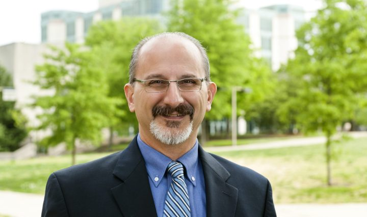 Man with glasses, mustache and short beard is wearing a blue suit and striped tie smiles at camera with green trees in the foreground.