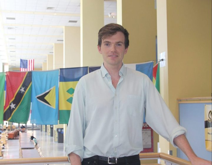 Man with brown hair, wearing a white dress shirt and black pants, with a row of international flags hanging in the background, smiles at camera.