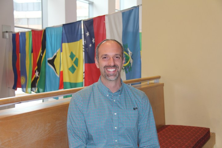 Man with grey hair and goatee, wearing a white and blue checkered shirt, stands smiling at camera with international flags in the background.