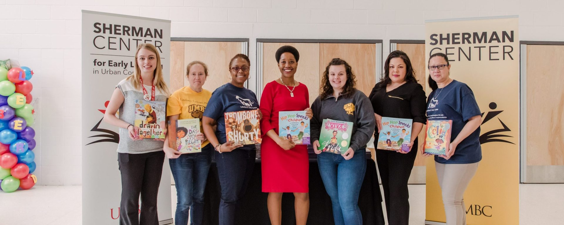 A group of woman of different races and ages stand next to eachother smiling at the camera while holding hard cover picture books in their hands. They are standing in between one white and one yellow standup banner with the words Sherman Center written on them.