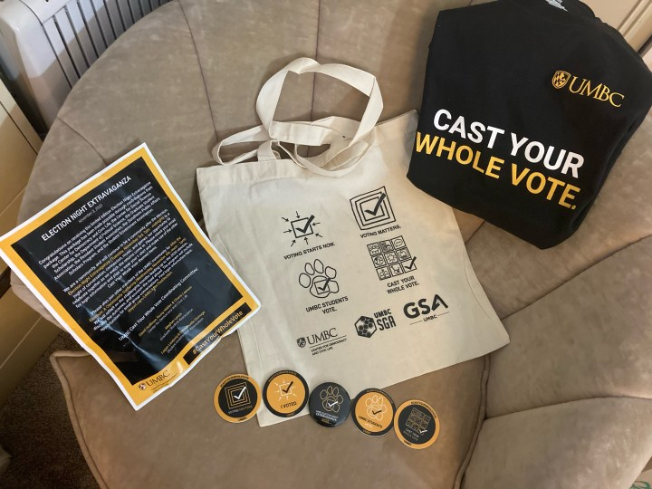 A gift bag, 5 buttons, flyers, and UMBC Cast Your Whole Vote t-shirt displayed on a chair.